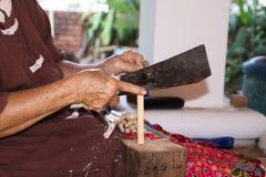 Mujer que parte un palillo de la madera de bambú con un cuchillo en la fábrica de papel del paraguas en Chiang Mai, Tailandia imagenes de archivo
