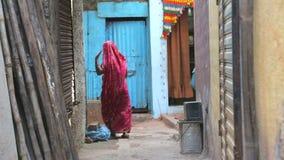Mujer que pasa a través de una calle estrecha en Bombay almacen de metraje de vídeo