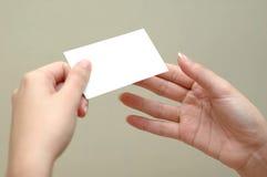 Mujer que pasa una tarjeta a otra mujer Fotos de archivo libres de regalías