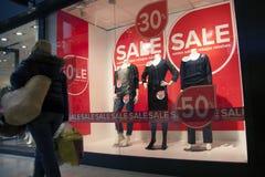 Mujer que pasa venta en el wndow de las compras de la tienda de la moda Fotografía de archivo libre de regalías