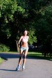Mujer que patina en parque Imagen de archivo libre de regalías