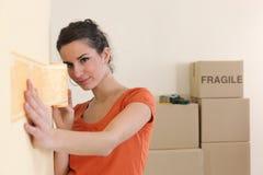Mujer que pega adorno del papel pintado Imagen de archivo libre de regalías