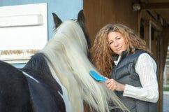 Mujer que peina la melena del caballo Fotografía de archivo libre de regalías