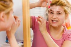 Mujer que pela apagado la máscara del gel de la cara Fotografía de archivo libre de regalías