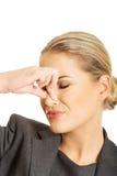 Mujer que pellizca la nariz debido a olor imagen de archivo