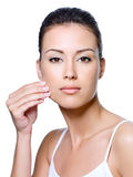 Mujer que pellizca la piel en su mejilla