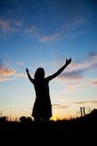 Mujer que permanece con las manos levantadas Fotografía de archivo libre de regalías