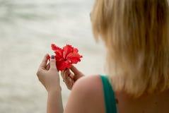 Mujer que permanece en una playa con la flor roja Foto de archivo libre de regalías