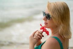 Mujer que permanece en una playa con la flor roja Imágenes de archivo libres de regalías