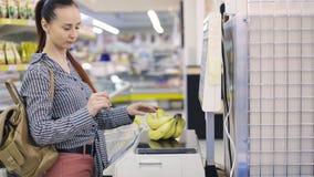 Mujer que pesa la comida en escala en el colmado almacen de video