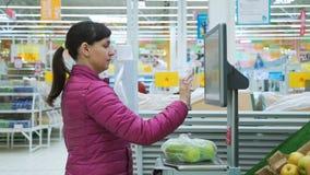 Mujer que pesa manzanas en escalas electrónicas metrajes