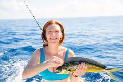 Mujer que pesca la captura feliz de los pescados de Dorado Mahi-mahi Foto de archivo