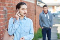 Mujer que pide ayuda en el teléfono móvil mientras que siendo acechado en C fotografía de archivo libre de regalías