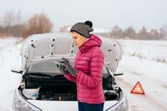 Mujer que pide la ayuda o la ayuda - avería del coche del invierno imagenes de archivo