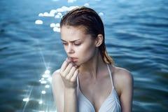Mujer que piensa con la natación mojada del pelo en el mar Fotografía de archivo