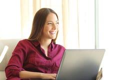 Mujer que piensa con un ordenador portátil en casa Foto de archivo libre de regalías