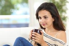 Mujer que piensa con una taza de café en casa Imagen de archivo