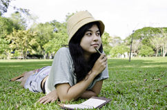 Mujer que piensa difícilmente estudiar afuera Foto de archivo libre de regalías