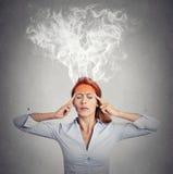Mujer que piensa el vapor demasiado duro que sale para arriba de la cabeza Foto de archivo libre de regalías