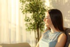 Mujer que piensa en la puesta del sol en casa Imágenes de archivo libres de regalías