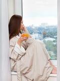 Mujer que piensa en la ventana. Foto de archivo libre de regalías