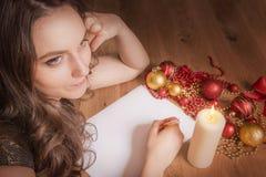 Mujer que piensa en una decoración de la Navidad fotos de archivo libres de regalías