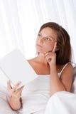 Mujer que piensa mientras que libro de lectura Fotos de archivo