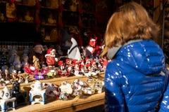 Mujer que piensa para comprar algunas decoraciones hechas a mano de la Navidad fuera de fotos de archivo libres de regalías
