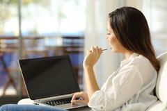 Mujer que piensa usando un ordenador portátil con la pantalla en blanco Imagen de archivo
