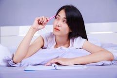 Mujer que piensa y que escribe un libro en su cama en dormitorio Foto de archivo libre de regalías