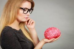 Mujer que piensa y que sostiene el cerebro falso Imagen de archivo