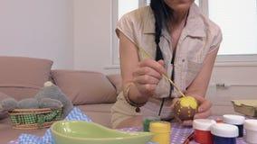 Mujer que pinta la flor amarilla en el huevo de Pascua