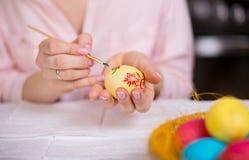 Mujer que pinta los huevos de Pascua Foto de archivo