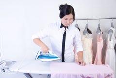 Mujer que plancha una camisa rosada imagen de archivo