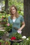Mujer que planta las flores en su jardín Fotos de archivo