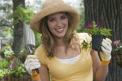Mujer que planta las flores en su jardín Foto de archivo