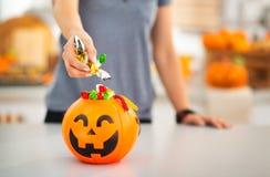 Mujer que pone el caramelo del truco o de la invitación en el cubo de Halloween primer Imagen de archivo