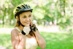 Mujer que pone el casco biking en exterior durante paseo de la bicicleta Fotografía de archivo