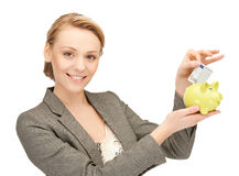 Mujer que pone el dinero del efectivo en la pequeña hucha Imagen de archivo
