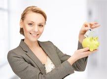 Mujer que pone el dinero del efectivo en la pequeña hucha Fotos de archivo
