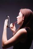 Mujer que pone el lápiz labial rojo que mira en espejo Imágenes de archivo libres de regalías