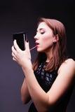 Mujer que pone el lápiz labial rojo que mira en espejo Foto de archivo