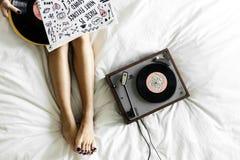 Mujer que pone en cama al lado del vinilo y de las notas musicales Imagenes de archivo