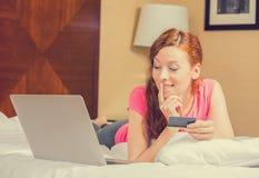 Mujer que pone en cama con el ordenador portátil que sostiene la tarjeta de crédito que hace compras en línea imágenes de archivo libres de regalías