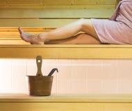 Mujer que pone en el banco de la sauna que lleva la toalla rosada Piernas largas que descansan y que se relajan Fotografía de archivo
