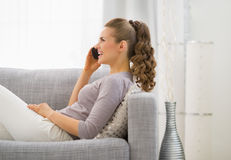 Mujer que pone en el diván y el teléfono móvil que habla imagen de archivo