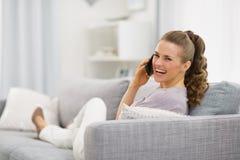 Mujer que pone en el diván y el teléfono móvil que habla fotografía de archivo