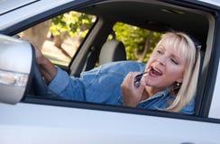 Mujer que pone en el lápiz labial mientras que conduce imagenes de archivo