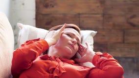 Mujer que pone en el sofá con dolor de cabeza metrajes
