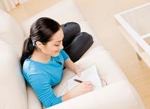 Mujer que pone en el sofá en la escritura de la sala de estar Imagen de archivo libre de regalías